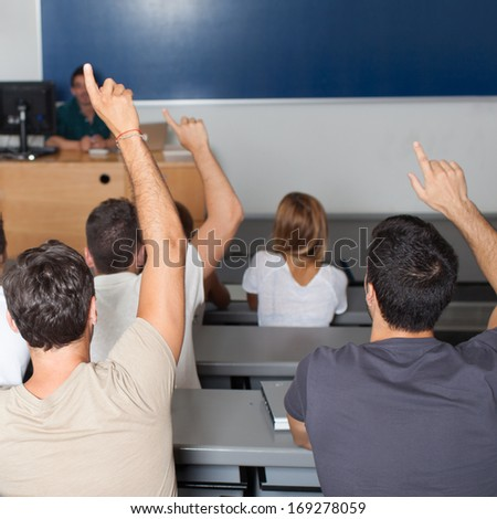 Students asking professor in classroom