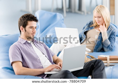 Students at high school or university working on laptop studying