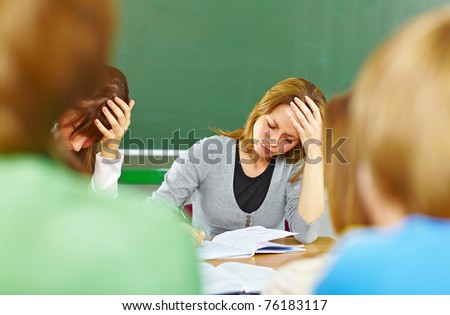 Students at the desk with notebook, struggling with school work - stock photo