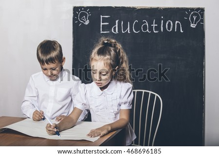 Students boy and girl in the class at the Desk on the background of the slate