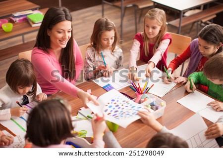 Students boys and girls sitting together around the table in classroom and drawing. With them is their young and beautiful teacher. She teaches children and is smiling - stock photo