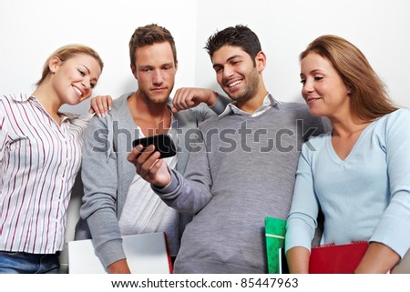 Students checking social network status updates on smartphone - stock photo