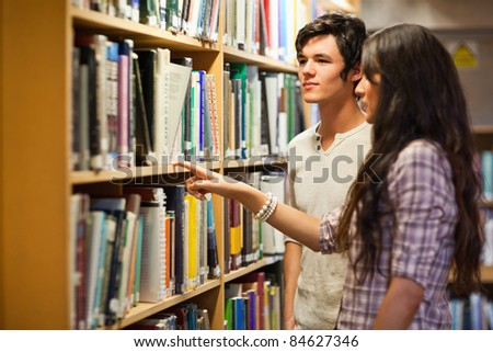 Students choosing a book in a library - stock photo