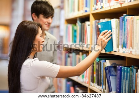 Students choosing a book on a shelf in a library