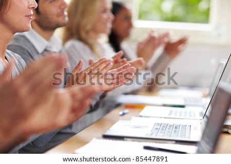 Students clapping hands for applause after university lecture - stock photo