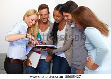 Students discussing assignments for class in university - stock photo