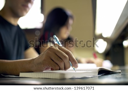 Students doing homework and preparing exam at university, closeup of young man writing in college library - stock photo