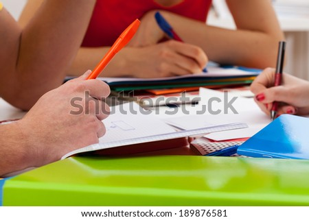 Students during writing important things in notebooks - stock photo