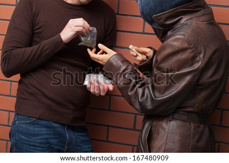 Students exchanging selected type of drugs for money - stock photo