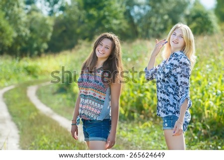 Students fiends in summer informal clothes are standing on country road near green corn field in checkered shirts and denim shorts. - stock photo
