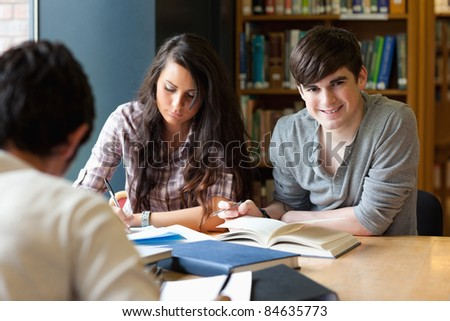 Students getting set for an assignment in a library - stock photo