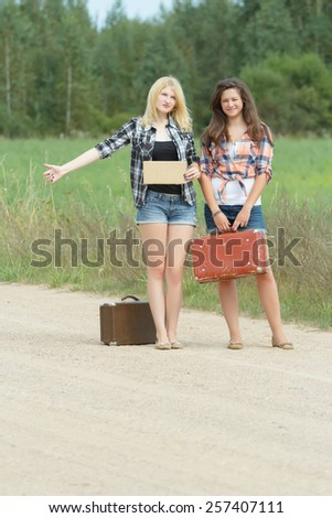 Students girls hitchhike with an empty cardboard - stock photo