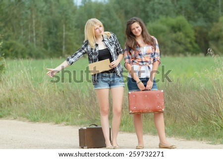 Students girls hitchhike with cardboard on a road - stock photo