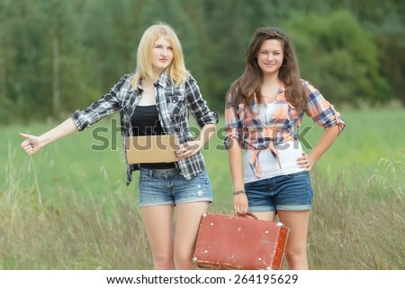 Students girls hitchhiking with cardboard on a road - stock photo