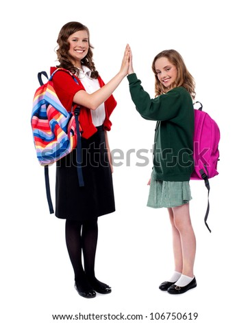 Students giving high five to each other and smiling. Full length portrait