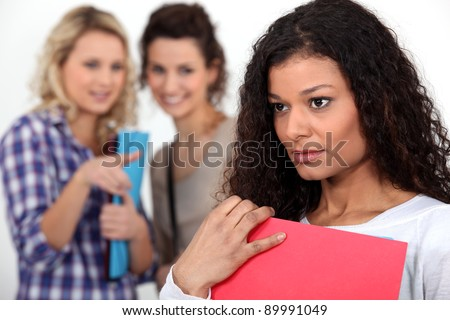 Students gossiping about a young woman - stock photo