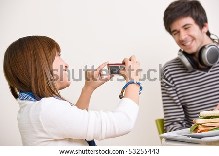Students - happy teenage couple taking photo with camera during lunch break in cafeteria