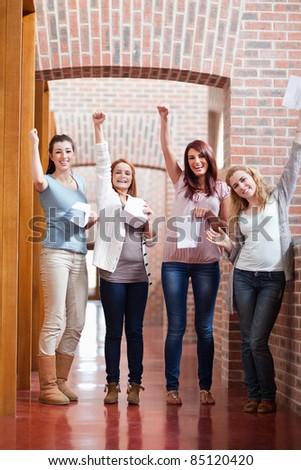 Students having good marks in a corridor - stock photo