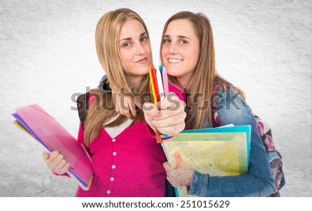 Students holding crayons over textured background - stock photo
