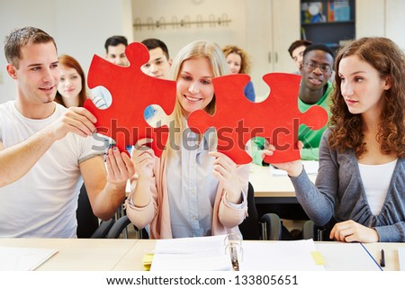 Students holding red oversized jigsaw puzzle in school class - stock photo