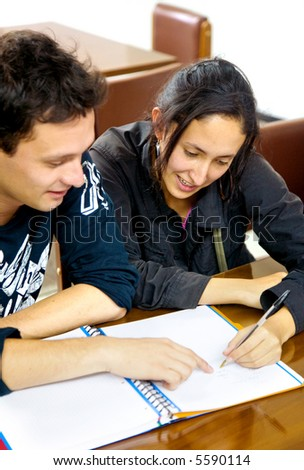 students in a library doing homework - both smiling - stock photo