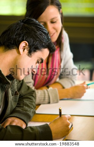 students in a library making notes on a notebook - stock photo