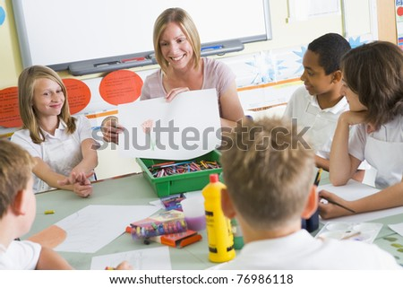 Students in art class with teacher showing a drawing - stock photo