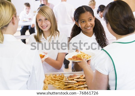 Students in cafeteria line being served by lunch ladies - stock photo