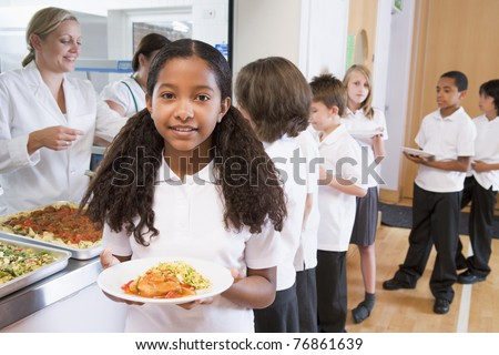 Students in cafeteria line with one holding her healthy meal and looking at camera - stock photo