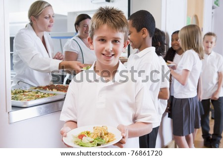 Students in cafeteria line with one holding his healthy meal and looking at camera - stock photo