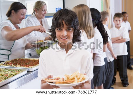 Students in cafeteria line with one holding his unhealthy meal and looking at camera - stock photo