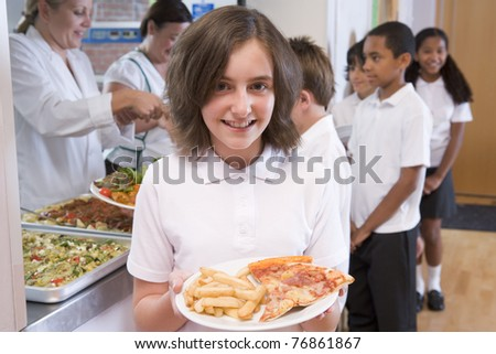 Students in cafeteria line with one holding unhealthy meal looking at camera - stock photo