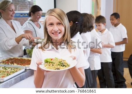 Students in cafeteria line with one holding up her healthy meal and looking at camera - stock photo