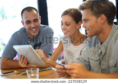 Students in campus lounge websurfing on tablet
