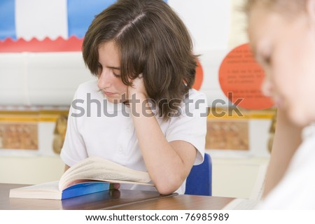 Students in class reading book (selective focus) - stock photo