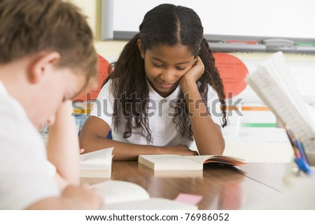 Students in class reading books (selective focus) - stock photo