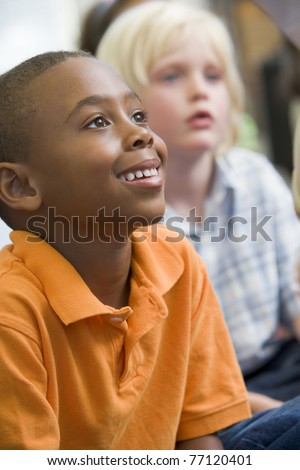 Students in class sitting on floor paying attention (selective focus) - stock photo