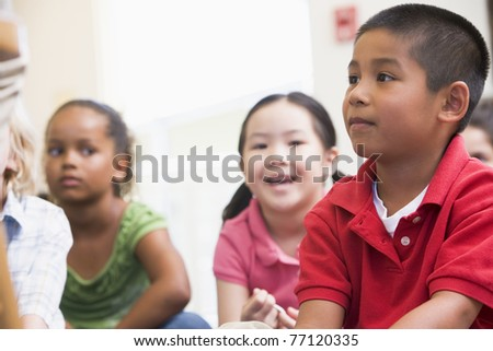 Students in class sitting on floor (selective focus) - stock photo