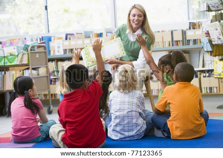 Students in class volunteering for teacher - stock photo