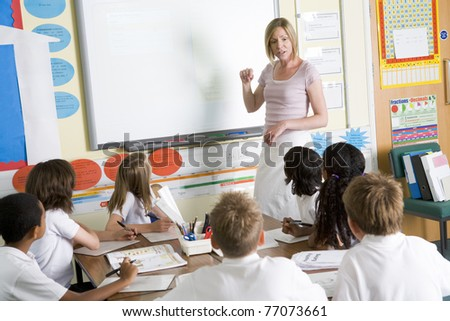 Students in class with teacher at board - stock photo