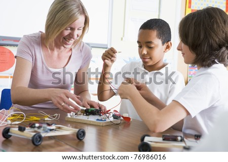Students in class with teacher making electronic cars - stock photo