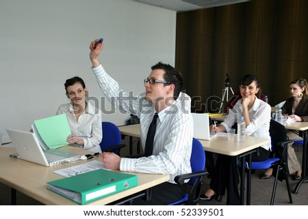 Students in classroom with a raised hand - stock photo