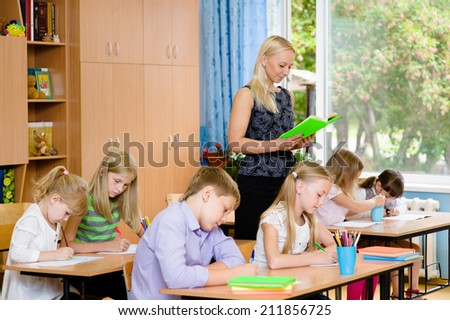 students in the class write assignments that reads them a young teacher - stock photo