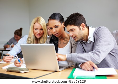 Students in university class learning at laptop - stock photo