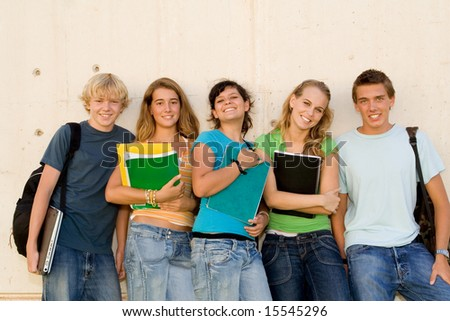 students leaning on school wall - stock photo