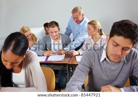 Students learning together in class at university - stock photo