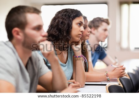 Students listening a lecturer in an amphitheater - stock photo