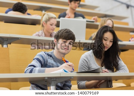 Students listening and taking notes in a lecture hall in college - stock photo