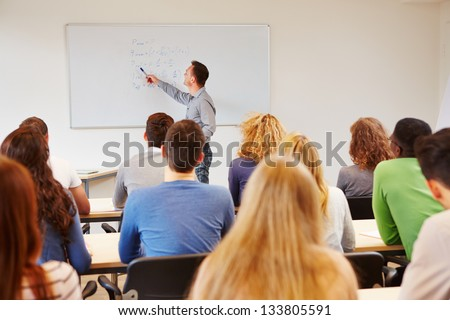 Students listening to teacher in class on a whiteboard - stock photo
