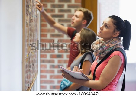 Students looking at notice board in college - stock photo